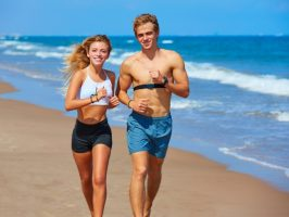 Blond young couple running on a beach in summer