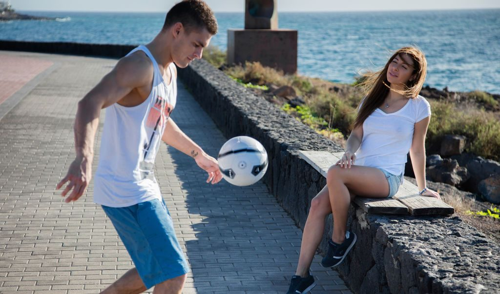 Couple playing football on the beachside